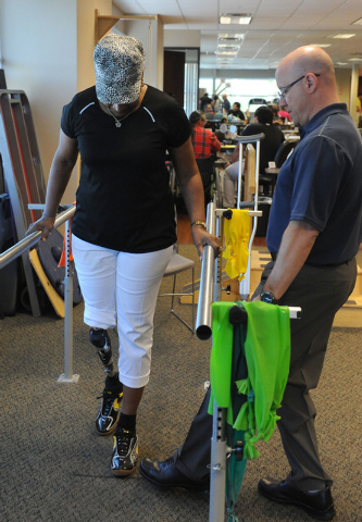 Elizabeth Bailey-Smith, left, is watched over by therapist Ed Dolegowski as she practices walking on her prosthetic leg at Matt Smith Physical Therapy, 7301 Peak Drive, Suite 101, June 6. Bailey-S ...