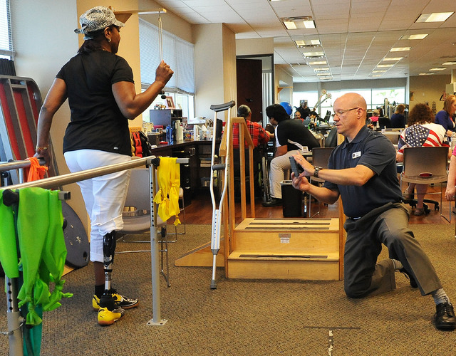 Therapist Ed Dolegowski, right, records Elizabeth Bailey-Smith's gait as she walks on her prosthetic leg at Matt Smith Physical Therapy,  7301 Peak Drive, Suite 101, June 6. Bailey-Smith had the p ...