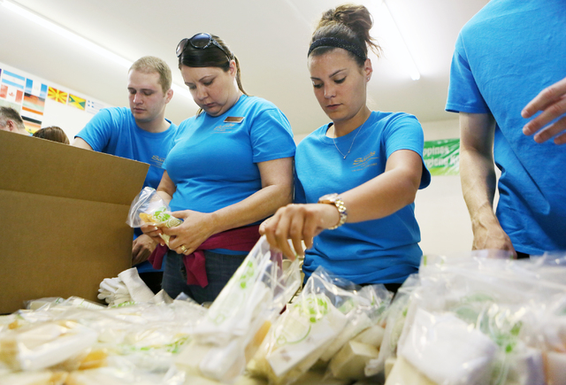 Las Vegas Sands Corporation employees Lucia Moody, left center, and Nicki Hankin, right center, assemble hygiene survival kits containing sanitized and recycled hotel soaps at Clean the World Wedn ...