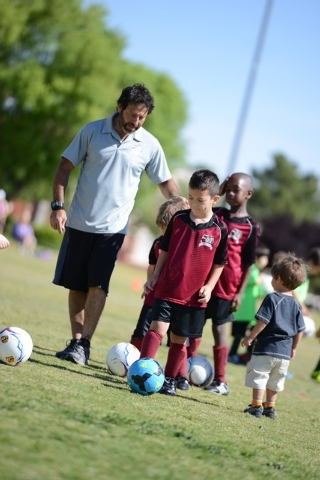 Musbah Eldik coaches his son's soccer team, the Strikers, June 17 at The Crossings Park. The soccer teams rely on fathers of players to help out in such capacities, only one example of what dads d ...