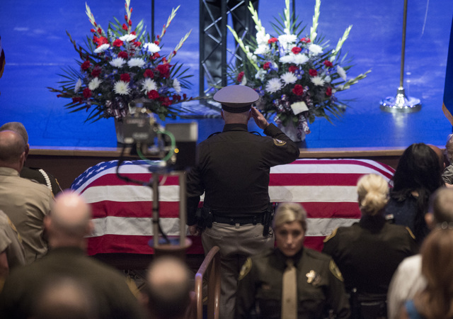 Las Vegas police officer salutes  the casket of fallen officer Igor Soldo,  at Canyon Ridge Christian Church,  6200 W Lone Mountain Road on Thursday, June 12,2014.  Soldo and officer Alyn Beck, 41 ...