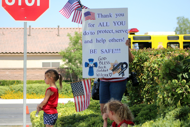 A family holds a sign after funeral services for Las Vegas police officer Igor Soldo at Palm Northwest Mortuary & Cemetery in Las Vegas on Thursday, June 12, 2014. Soldo, 31, and fellow officer, A ...