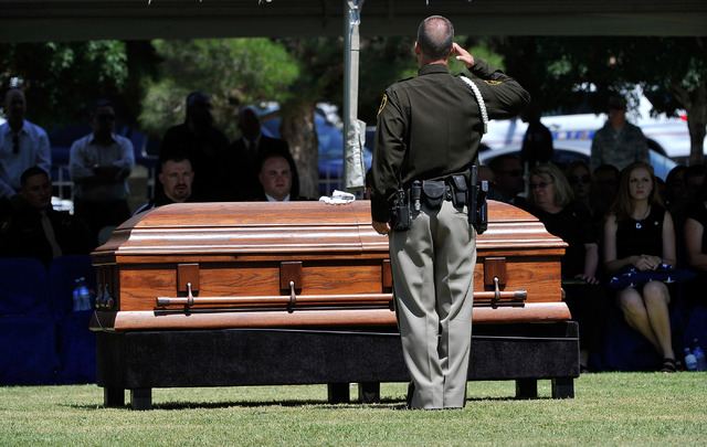 A Las Vegas police officer salutes the casket of Las Vegas police officer Igor Soldo during funeral services for him at Palm Northwest Mortuary & Cemetery on Thursday, June 12, 2014 in Las Vegas.  ...