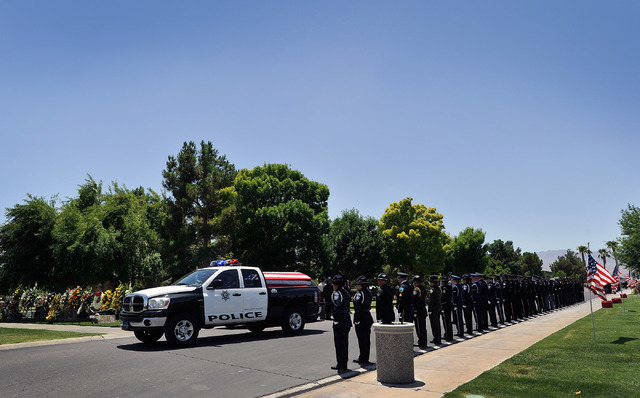The casket of Las Vegas police officer Igor Soldo arrives aboard a police vehicle for funeral services at Palm Northwest Mortuary & Cemetery on Thursday, June 12, 2014 in Las Vegas. Soldo, 31, and ...
