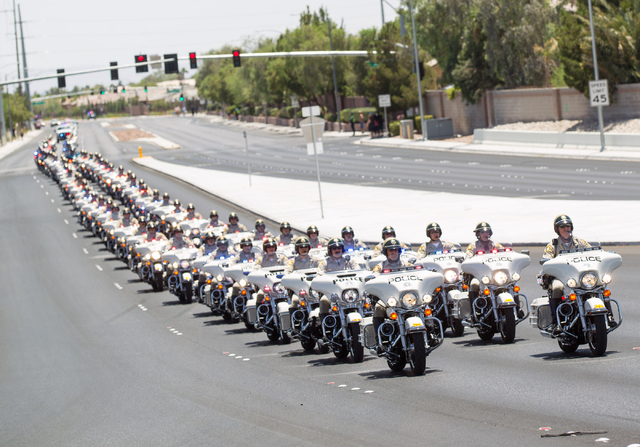 Law enforcement officers on motorcycles lead a funeral procession for fallen Las Vegas police officer Igor Soldo on Jones Boulevard toward Palm Northwest Mortuary & Cemetery in Las Vegas on Thursd ...