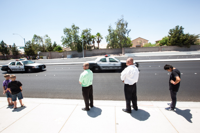 People watch as a funeral procession for fallen Las Vegas police officer Igor Soldo heads north on Jones Boulevard toward Palm Northwest Mortuary & Cemetery in Las Vegas on Thursday, June 12, 2014 ...