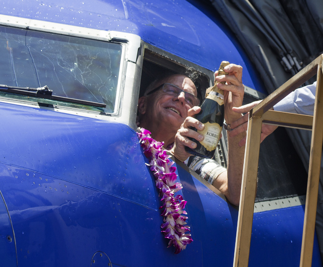 Southwest Airline  pilot Capt. Fred Sorenson opens a bottle of sparkling wine at  McCarran International Airport after making his final flight for the airlines on Wednesday, June 11 , 2014.  Soren ...