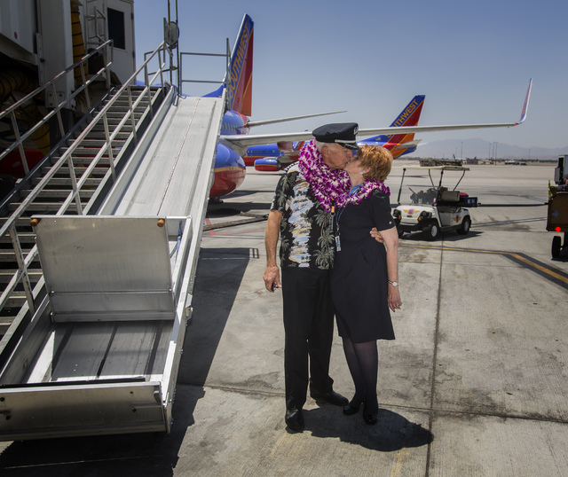 Southwest Airline  pilot Capt. Fred Sorenson,left, kisses head flight attendant Pat Schader on the tarmac  at  McCarran International Airport after making his final flight with the airlines on Wed ...