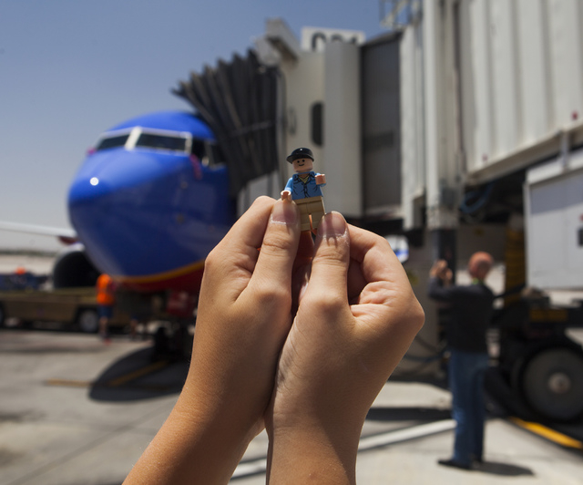 Jeremy Stanton, 10, holds a LEGO Indiana Jones  Jock character in front of a  Southwest Airline flown by Capt. Fred Sorenson at  McCarran International Airport on Wednesday, June 11 , 2014. Sorens ...