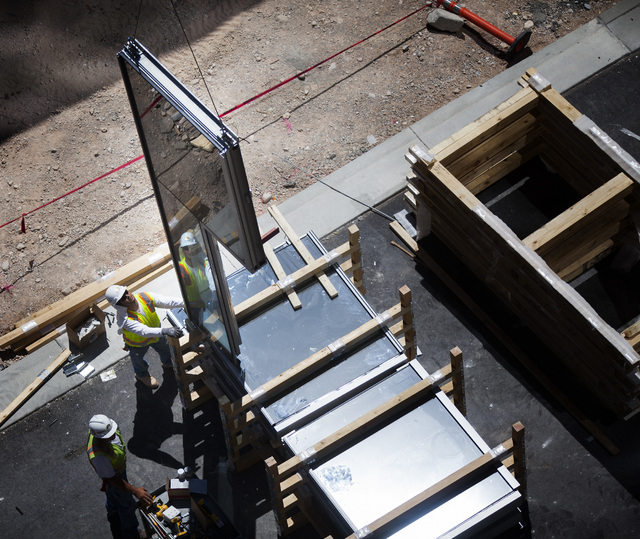A construction works guide a glass panel  at  Downtown Summerlin at Sahara Avenue and I-215 on Thursday, May 15, 2014. The first phase of the development will include 1.6 million square feet on re ...