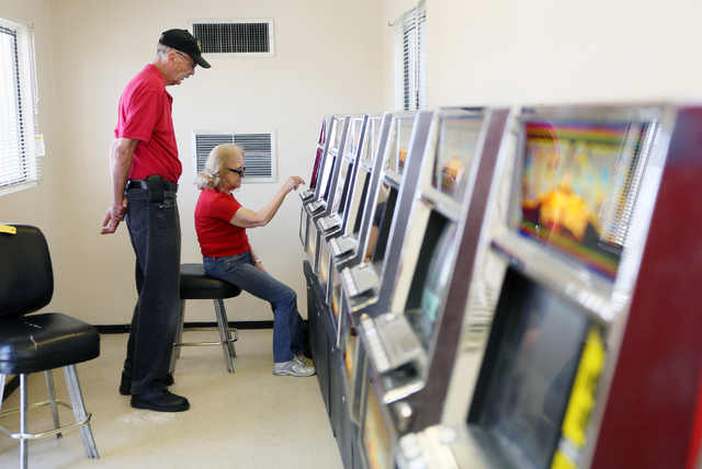 Ben Blackford, left, a United Coin Machine Co. slot technician, offers guidance to Louise Yokshus (cq)  while she plays poker at a modular building at Moulin Rouge, located at 900 West Bonanza Rd. ...