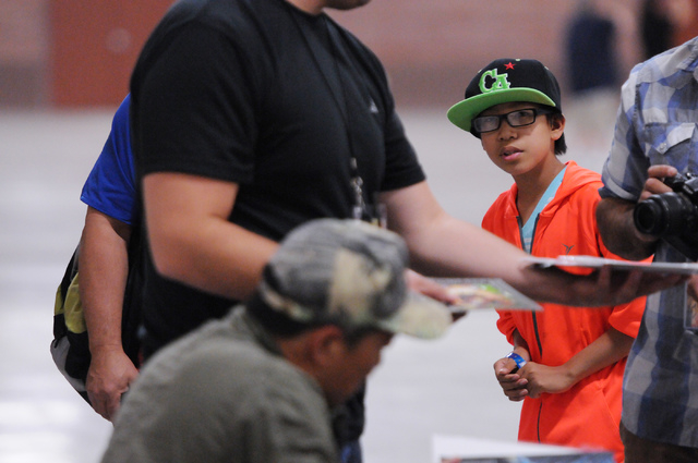 Christian McGonagle, 10, waits in line for an autograph from comic book illustrator and publisher Jim Lee during the 2014 Amazing Las Vegas Comic Con at South Point casino-hotel in Las Vegas Satur ...