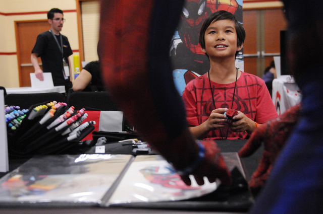 Artist Ethan Castillo, 9, speaks with Brett Adams, in character as Spiderman, as he browses his work during the 2014 Amazing Las Vegas Comic Con at South Point casino-hotel in Las Vegas Saturday,  ...