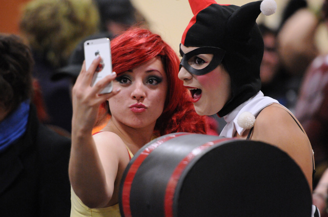 Jenny Egidio, left, in character as Misty from Pokémon, and her friend Miranda Cooper, in character as Harley Quinn, take a photo together as they wait line to participate in the costume cont ...