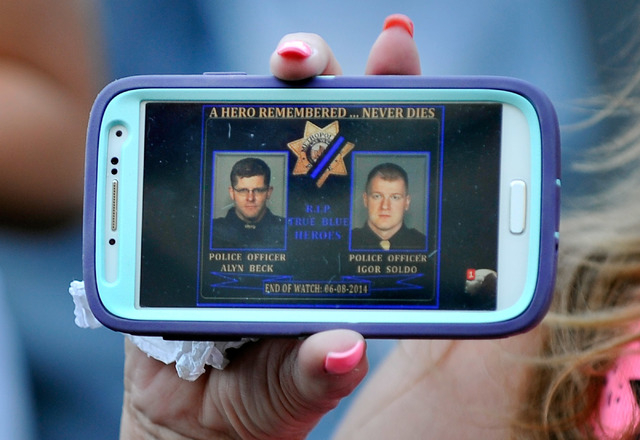 Regen Hardt holds her smart phone with an image of the two slain officers during a candlelight vigil at CiCi's Pizza at 309 N. Nellis Blvd. on Monday, June 9, 2014.  Las Vegas police officers Alyn ...