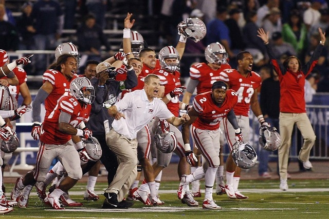 UNLV head coach Bobby Hauck, middle in white, rushes onto the field to celebrate with his players as the clock winds down against UNR at Mackay Stadium in Reno on Oct. 26, 2013. The NCAA is expect ...