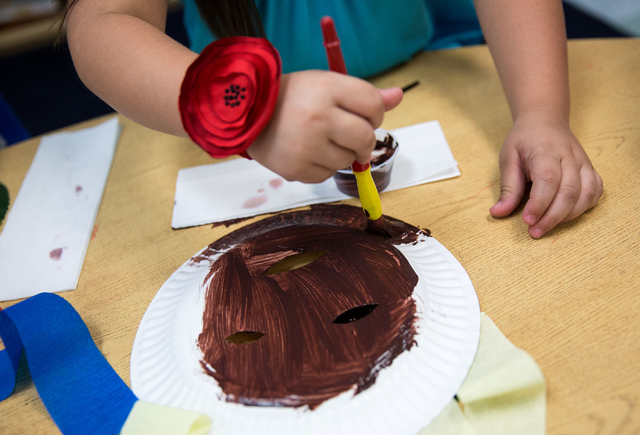 Izabella Hernandez paints a mask during Shenker Academy's summer camp. (Samantha Clemens-Kerbs/Las Vegas Review-Journal)