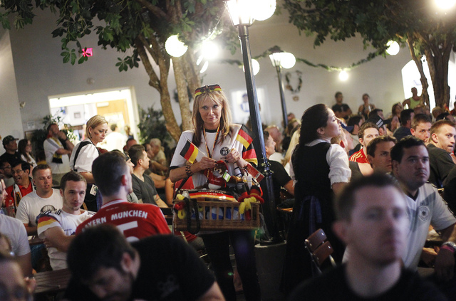 Judy (last name withheld), center, tries to sell German-themed merchandise during the World Cup soccer game between Germany and Ghana at the Hofbrauhaus in Las Vegas on June 21, 2014. (Jason Bean/ ...
