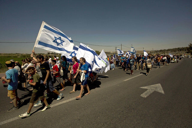 Israelis march on the road near where three missing teenagers were abducted, June 12, near the West Bank Jewish settlement of Alon Shvut , Tuesday, July 1, 2014. The Israeli military found the bod ...