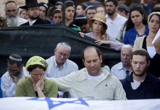 Avi and Rachel Fraenkel attend the funeral of their son, Naftali, a 16-year-old with dual Israeli-American citizenship, in the West Bank Jewish settlement of Nof Ayalon, Tuesday, July 1, 2014. The ...