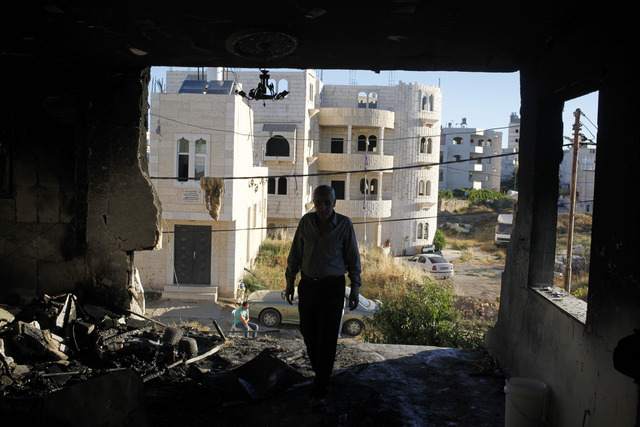 A Palestinian inspects the damaged family home of Amer Abu Aisheh, one of two Palestinians identified by Israel as suspects in the killing of three Israeli teenagers, after it was damaged by the I ...