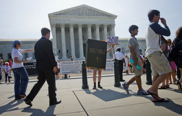 A demonstrator dressed as the 'Bible' stands outside the Supreme Court in Washington, Monday, June 30, 2014, awaiting the court's decision on the Hobby Lobby case. The Supreme Court says corporati ...