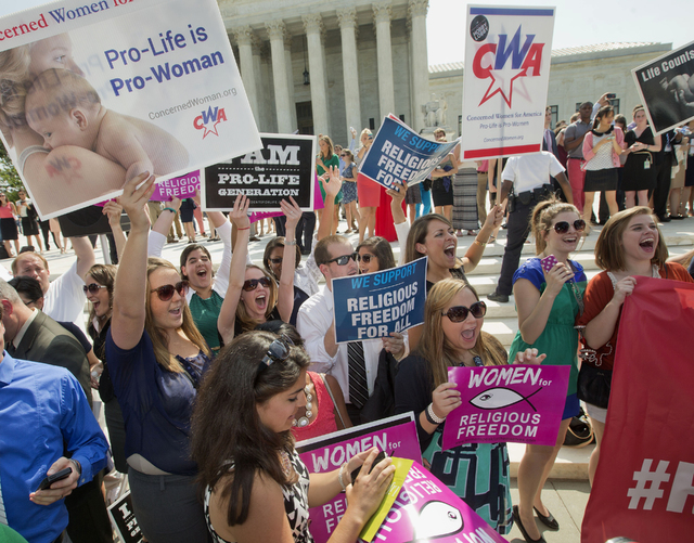 Demonstrator react to hearing the Supreme Court's decision on the Hobby Lobby case outside the Supreme Court in Washington, Monday, June 30, 2014. The Supreme Court says corporations can hold reli ...