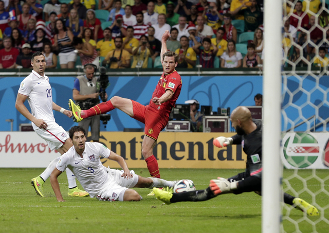 United States' Omar Gonzalez (3) and Geoff Cameron (20) watch as goalkeeper Tim Howard makes a save on Belgium's Jan Vertonghen shot on goal during the World Cup round of 16 soccer match between B ...