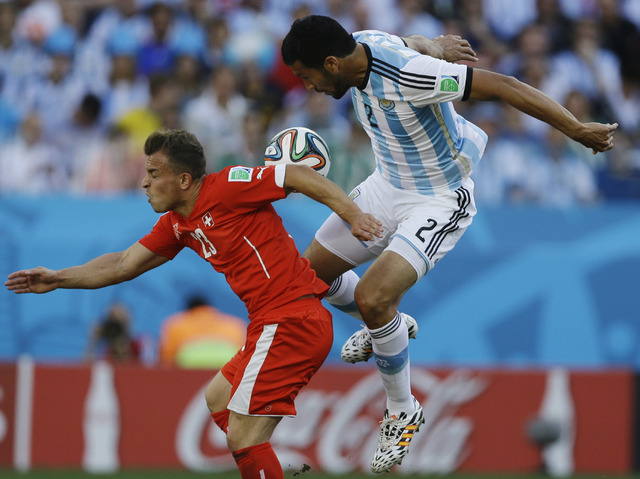 Switzerland's Xherdan Shaqiri, left, and Argentina's Ezequiel Garay go for a header during their World Cup round of 16 soccer match at the Itaquerao Stadium in Sao Paulo, Brazil, Tuesday, July 1,  ...