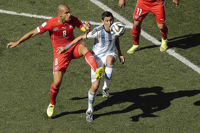 Switzerland's Goekhan Inler, left, and Argentina's Angel di Maria challenge for the ball during the World Cup round of 16 soccer match between Argentina and Switzerland at the Itaquerao Stadium in ...