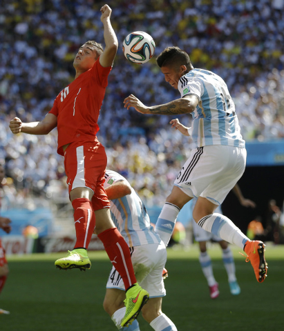 Argentina's Marcos Rojo, right, and Switzerland's Granit Xhaka go for a header during their World Cup round of 16 soccer match at the Itaquerao Stadium in Sao Paulo, Brazil, Tuesday, July 1, 2014. ...