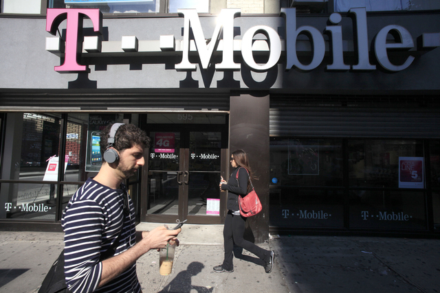 A man uses a cellphone as he passes a T-Mobile store in New York in this September 12, 2012, file photo. T-Mobile USA knowingly made hundreds of millions off its customers in bogus charges, a fede ...