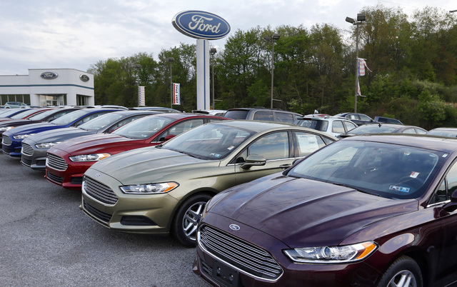 In this Wednesday, May 8, 2013 photo, new 2013 Ford Fusions are seen at an automobile dealer in Zelienople, Pa. U.S. auto sales slowed slightly in June 2014 but still maintained a healthy pace des ...