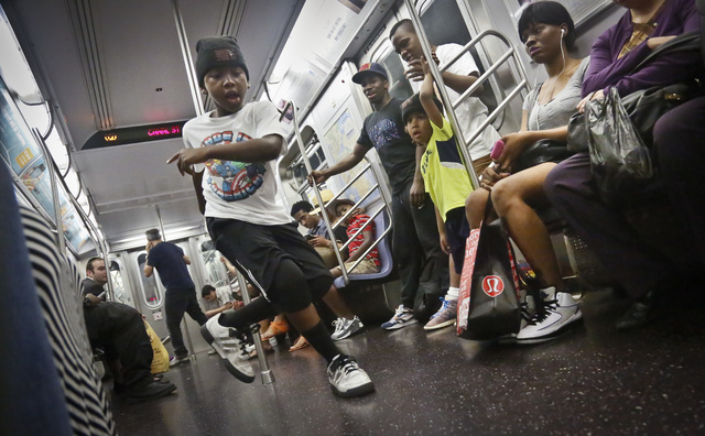 "In this June 17, 2014 photo, Marc Mack, 8, a member with the dance troupe W.A.F.F.L.E., performs on a subway, in New York. Police Commissioner William Bratton's department ""broken window&quot ..."
