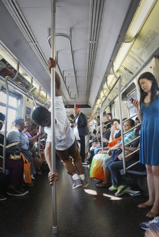 Andrew Sanders, center, leader of the group W.A.F.F.L.E., which stands for We Are Family For Life Entertainment, performs acrobatic dance on a subway, in New York on June 17. His troupe, which has ...