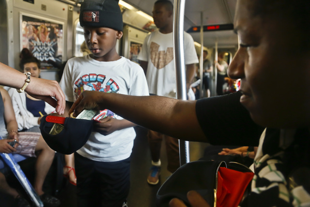 Marc Mack, 8, a member with the dance troupe W.A.F.F.L.E., which stands for We Are Family For Life Entertainment, collects money from subway riders after a performance in New York on June 17. (AP  ...