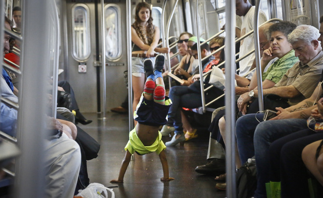Acrobatic dancer Nasir Malave, 5, dances on a subway train in New York on June 17. The New York Police Department is cracking down on the subway showmen who use the tight quarters of the nations b ...