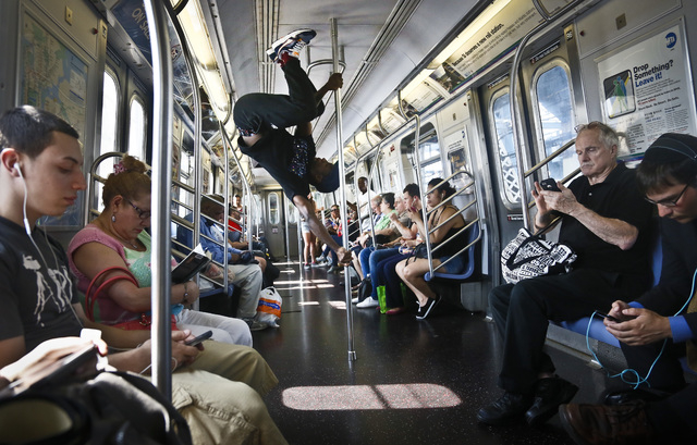 Dashawn Martin, center, a member with the dance troupe W.A.F.F.L.E., which stands for We Are Family For Life Entertainment, performs on a subway, in New York on June 17. The subway acrobats said t ...