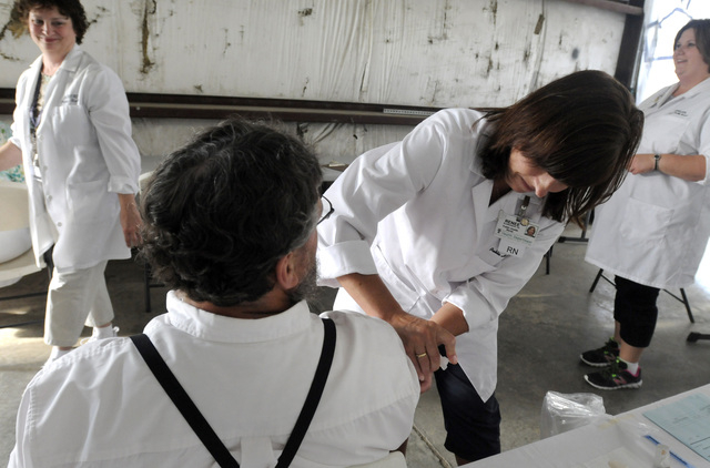 Richland Public Health nurse Renee Blankenship gives Daniel Martin, an Amish man from Holmes County, his measles, mumps and rubella (MMR) vaccination while he talks with nurses Sue McFarren, left, ...