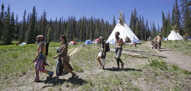 People walk along a trail in the Rainbow Family encampment Tuesday, July 1, 2014, in the Uinta National Forest, Utah. About 4,000 members of a counterculture group known as the Rainbow Family have ...