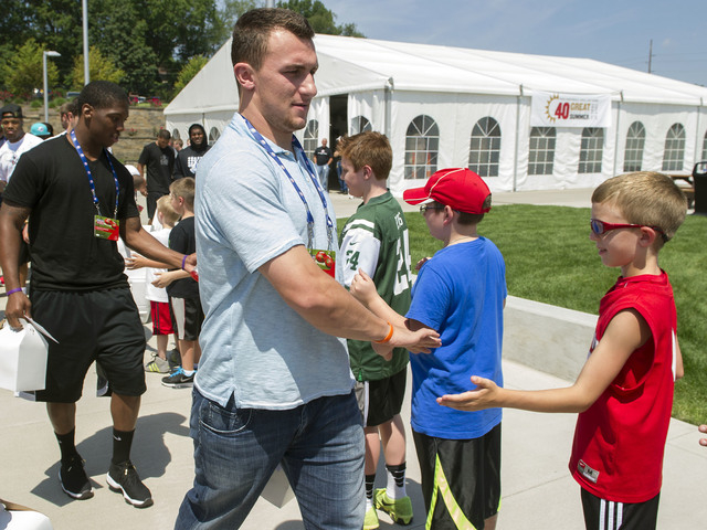 Cleveland Browns rookie Johnny Manziel greets fans as he leaves the 2014 NFL Rookie Symposium at the Pro Football Hall of Fame in Canton, Ohio, Saturday, June 28, 2014. (AP Photo/Phil Long)