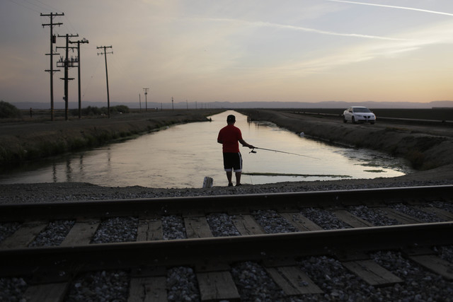 Rigoberto Arroyo, 18, fishes from a canal in Mendota, Calif., on May 3. Throughout California's dry interior, those with water to spare are cashing in on the drought. As a third dry summer forces  ...