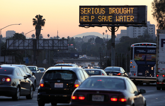 Morning traffic makes its way toward downtown Los Angeles along the Hollywood Freeway past an electronic sign warning of severe drought on Feb. 14. Los Angeles has concluded another rain season wi ...