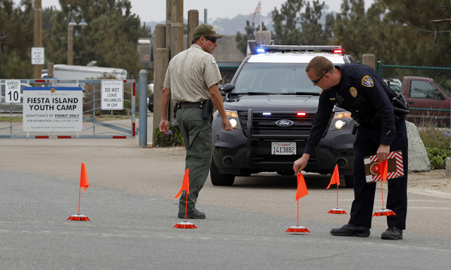 Police block the main entrance to the Fiesta Island Youth Camp where a boy died from a self-inflicted gunshot wound at a Boy Scout camp on Monday, June 30, 2014. The 12-year-old boy died from a gu ...