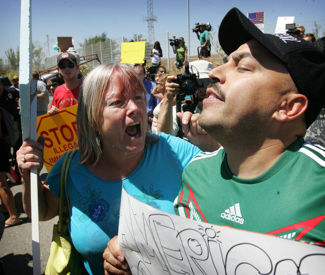An unidentified protester, left, argues with American citizen Lupillo Rivera, brother of Mexican-American singer Jenni Rivera, right, as three buses carrying 140 immigrants attempt to enter the Mu ...