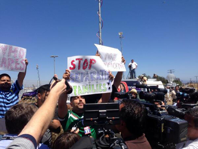 Counter-protestors hold pro-immigrant banners as protestors stand in the road blocking a bus carrying 140 immigrants on the way to be processed at the Murrieta border patrol station on Tuesday, Ju ...