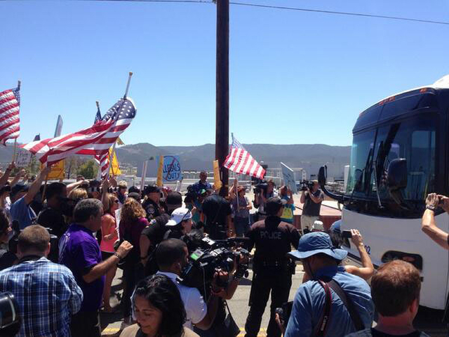 Protesters stand in the road blocking a bus carrying 140 immigrants on the way to be processed at the Murrieta border patrol station on Tuesday, July 1, 2014. The immigrants are bused to a border  ...