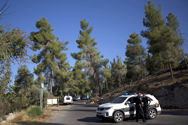 Israeli police officers block the entrance to a forest, where a body was found, in Jerusalem, Wednesday, July 2, 2014. Israeli police say Palestinians and Israeli forces have clashed following rep ...