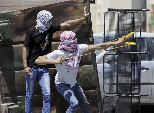 A Palestinian uses a sling shot during clashes with Israeli border police in Jerusalem on Wednesday, July 2, 2014. The suspected abduction of an Arab teen followed by the discovery of a body in Je ...
