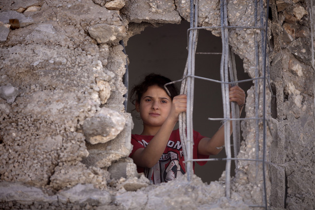 Mai Awad looks out from the damaged family home of Palestinian Ziad Awad in the town of Idna,13 kilometers (8 miles) west of the West Bank city of Hebron, Wednesday, July 2, 2014. Israel demolishe ...